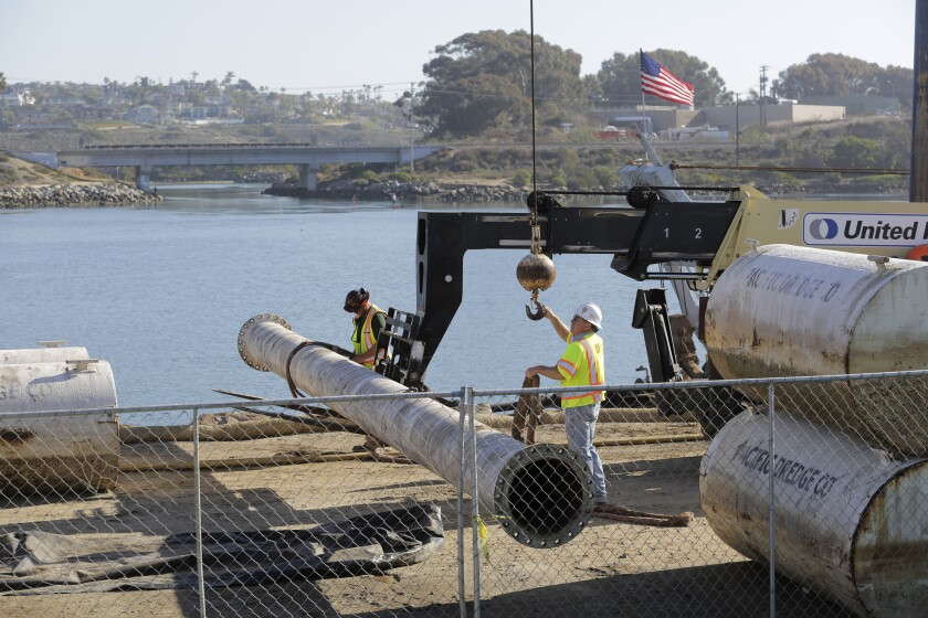 Workers move sections of pipe at the west edge of Agua Hedionda Lagoon in Carlsbad Friday. photo by Bill Wechter