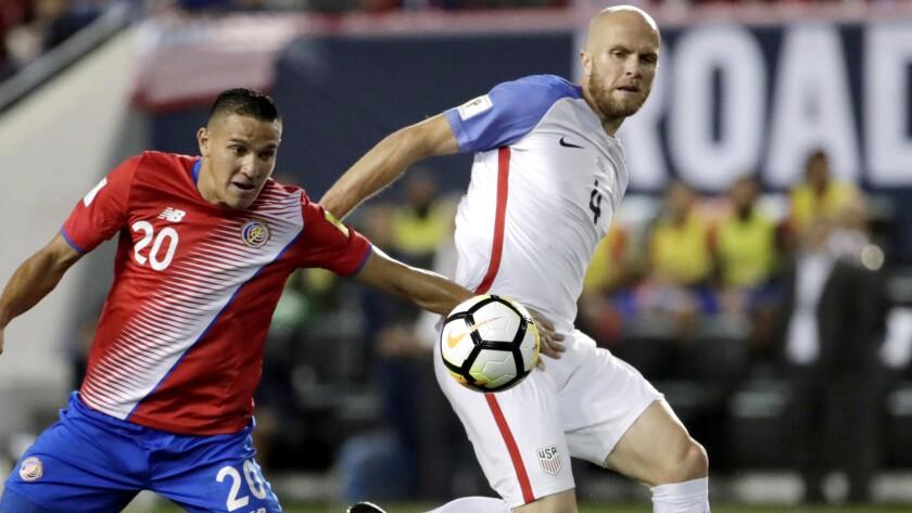 Costa Rica midfielder David Guzman, left, and U.S. midfielder Michael Bradley compete for the ball d