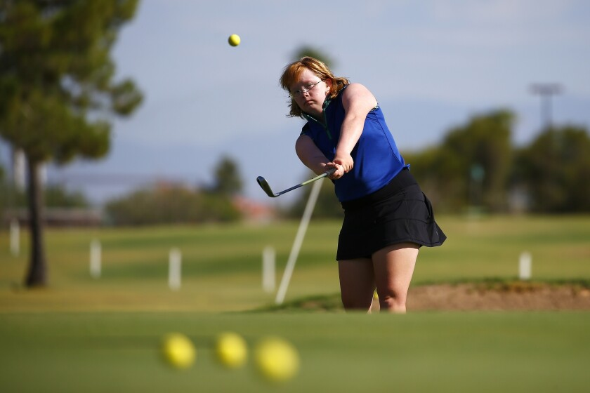 In this Aug. 28, 2019, file photo, Amy Bockerstette practices with her teaching pro at Palmbrook Country Club in Sun City, Ariz. Bockerstette is set to become the first person with Down syndrome to compete in a national collegiate athletic championship. (AP Photo/Ross D. Franklin, File)