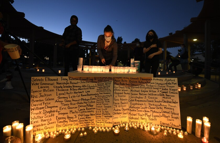 People lit candles around sign listing names of people who suffered from police brutality.