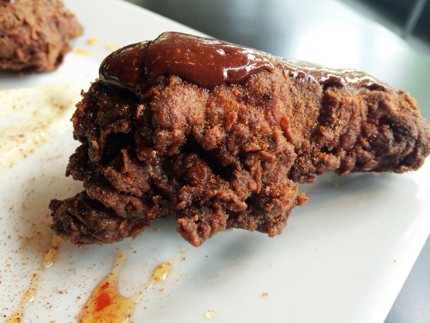 Chocolate fried chicken with chocolate ketchup on top.