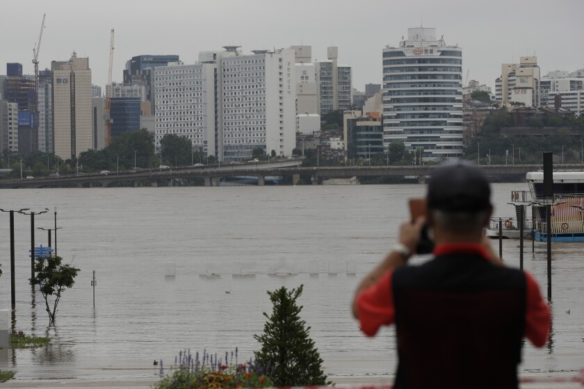 The display of South Korea's capital Seoul logo is almost submerged due to heavy rain at a park near the Han River in Seoul, South Korea, Thursday, Aug. 6, 2020. Torrential rains continuously pounded South Korea on Thursday, prompting authorities to close parts of highways and issue a rare flood alert near a key river bridge in Seoul. (AP Photo/Lee Jin-man)