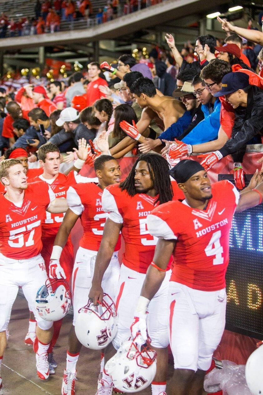 Houston players greet hands fans after an NCAA college football game against Cincinnati at TDECU Stadium, Saturday, Nov. 7, 2015, in Houston. Houston defeated Cincinnati 33-30. (AP Photo/Juan DeLeon)