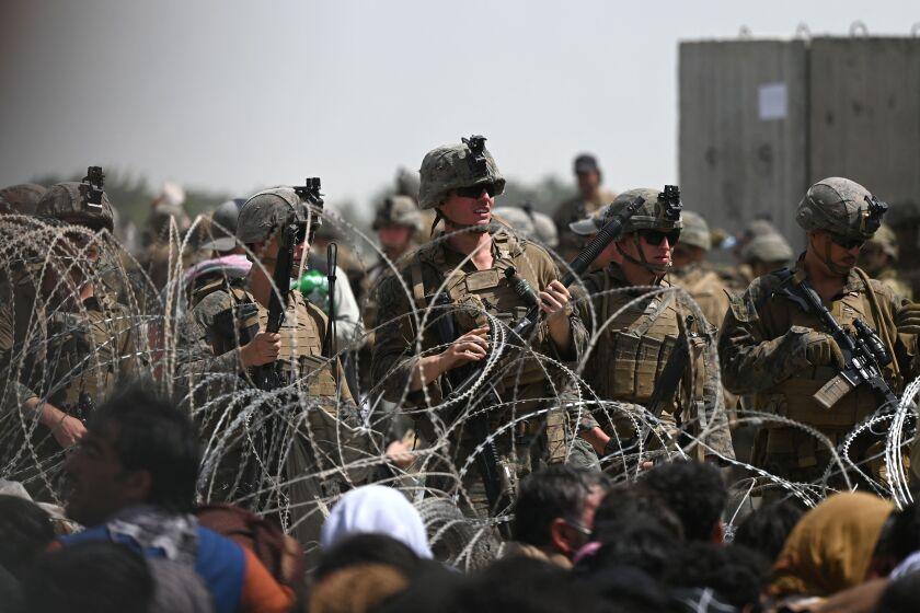 سربازان آمریکایی پشت سیم خاردار نگهبانی می دهند در حالی که افغان ها در جاده ای نزدیک ارتش فرودگاه کابل نشسته اند