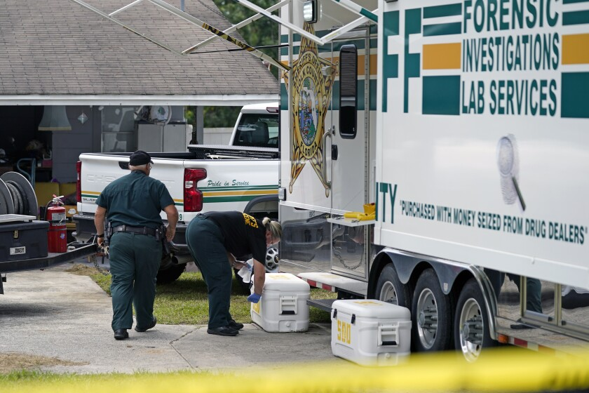 Officers from the Polk County Sheriff Department work outside Tuesday, Sept. 7, 2021, in Lakeland, Fla., at the home where a family of four was shot and killed. (AP Photo/John Raoux)