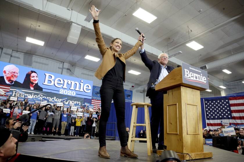 Democratic presidential candidate Sen. Bernie Sanders (I-Vt.) and Rep. Alexandria Ocasio-Cortez (D-N.Y.) greet supporters Nov. 8 at Iowa Western Community College in Council Bluffs, Iowa.