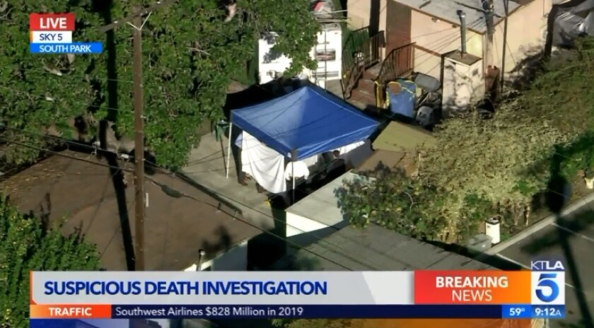 Authorities work under a tent at a home in South Los Angeles on Thursday after bones were discovered at the property.