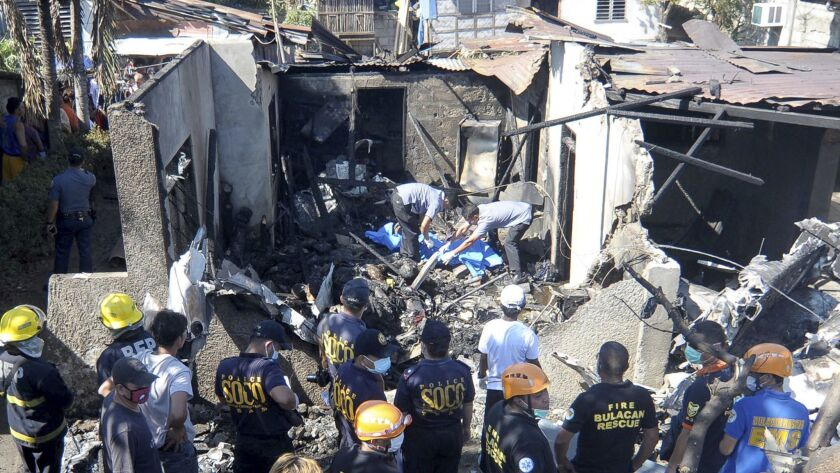 Rescuers sift through the debris after the crash upon takeoff of a Piper-23 Apache aircraft in Plaridel township north of Manila.