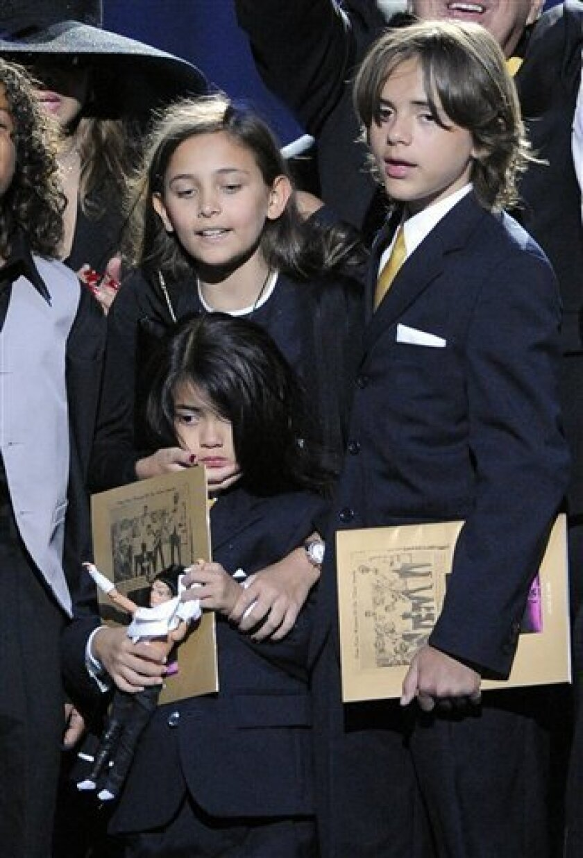 FILE - In this July 7, 2009 file photo, Paris Jackson, left, Prince Michael Jackson II and Prince Michael Jackson I, stand on the stage during the memorial service for Michael Jackson at the Staples Center in Los Angeles. (AP Photo/Mark J. Terrill, file)