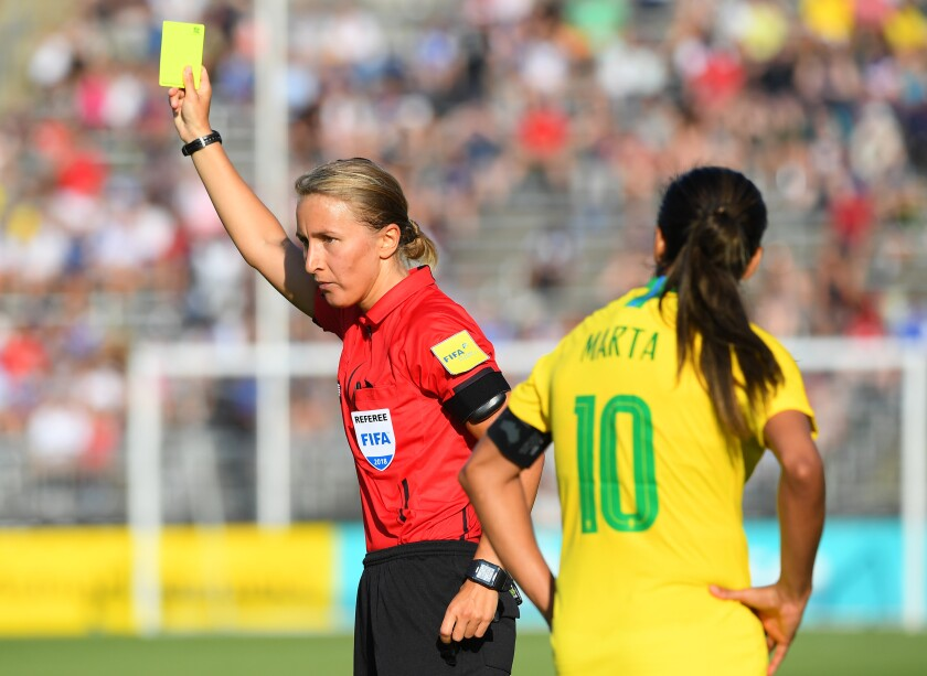 Referee Katja Koroleva issues a yellow card to Brazil's Raquel (not pictured) as teammate Marta reacts against Japan during the second half of a Tournament of Nations game played at Pratt & Whitney Stadium on July 29, 2018 in East Hartford, Conn.