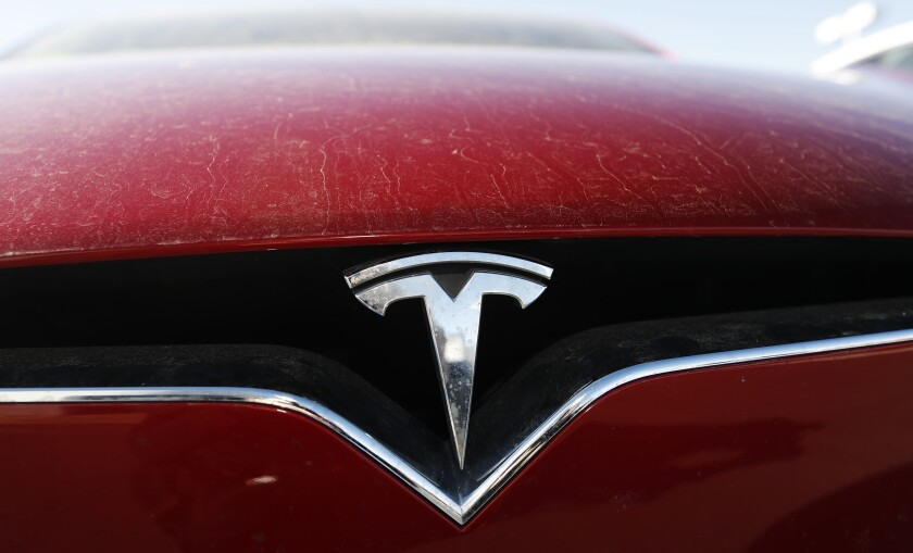 FILE - In this Feb. 2, 2020, file photo, the company logo shines on the grille of an unsold 2020 Model X at a Tesla dealership in Littleton, Colo. Tesla is now worth more than General Motors, Ford and Fiat Chrysler combined, even though the Big Three together sell more cars and trucks in two weeks than Tesla does in a whole year. (AP Photo/David Zalubowski, File)