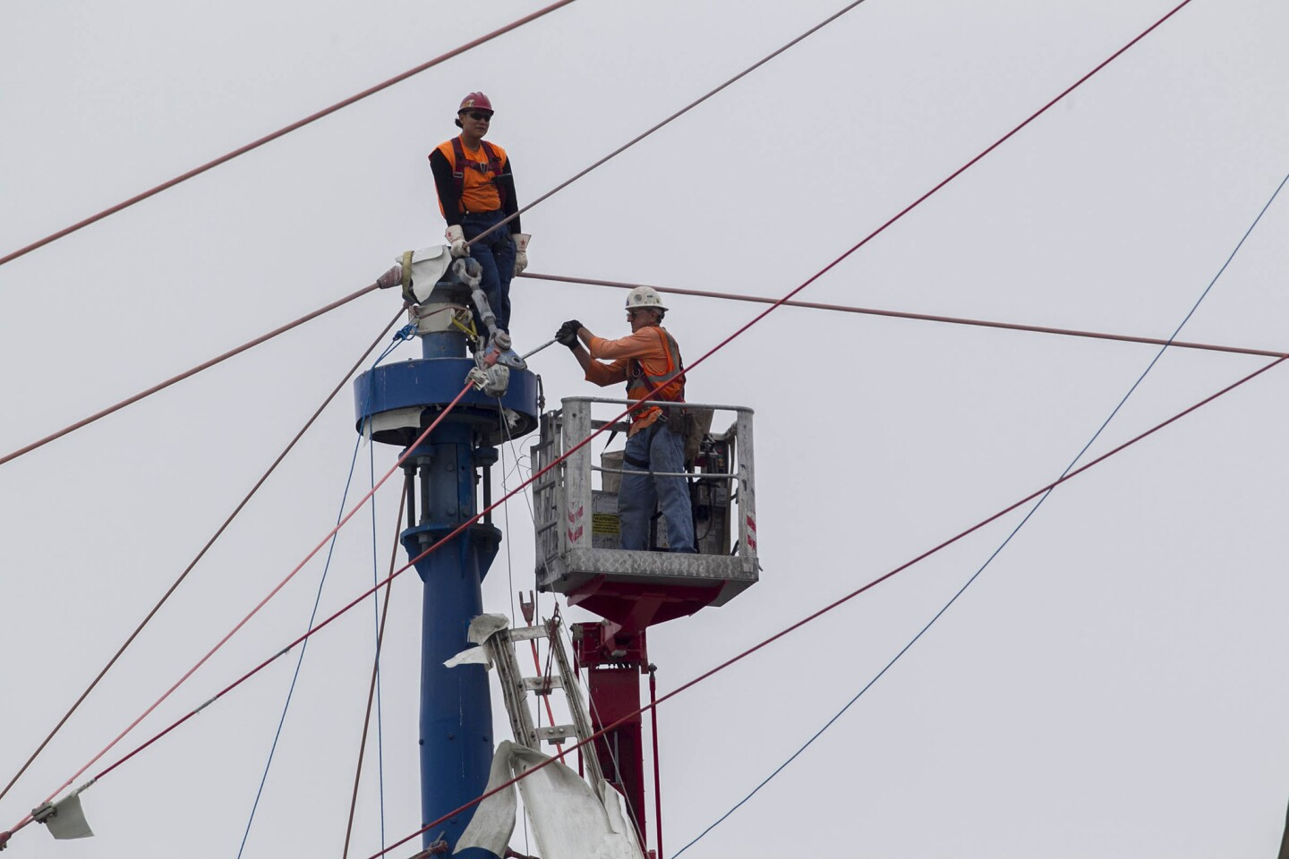 Workers lowered a disconnected section of the roof rigging.