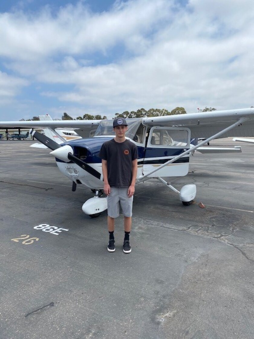 La Jolla High School student Charlie Lansky stands with the Cessna plane in which he is learning to fly.