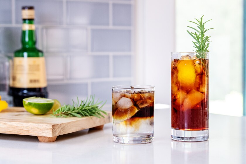 A cutting board with ingredients, left, and two coffee tonic cocktails in glasses.