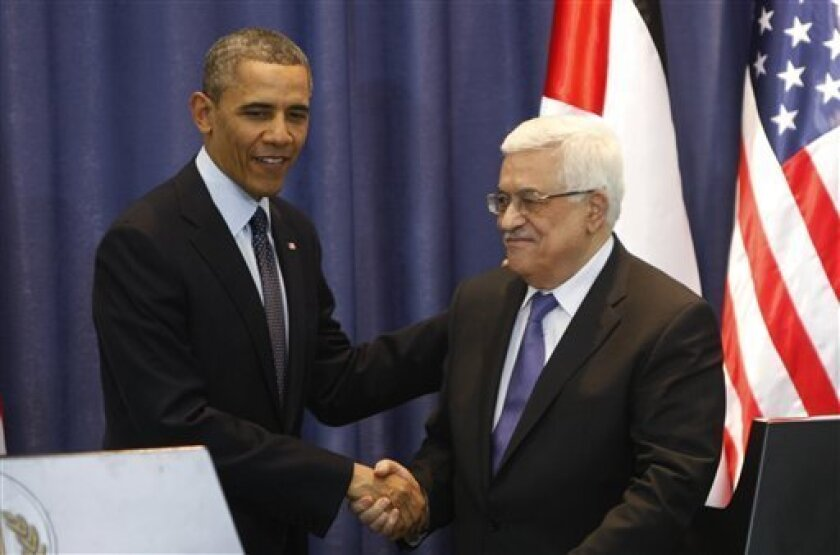 US President Barack Obama, left, shakes hands with Palestinian President Mahmoud Abbas during a joint press conference in the West Bank city of Ramallah, Thursday, March. 21, 2013. Obama on Thursday urged Israelis and Palestinians to get back to peace talks but offered no new ideas on how they migh