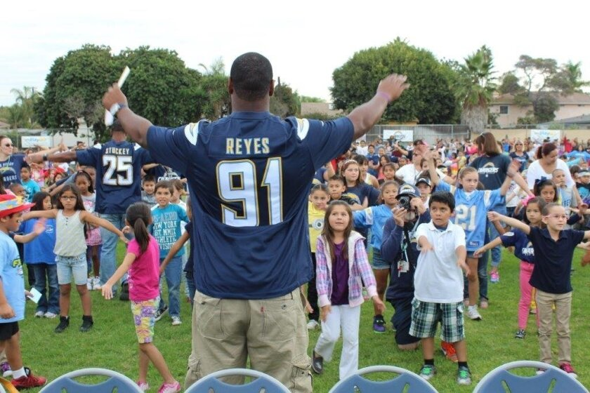 Chargers defensive end Kendall Reyes works out with students at Oneonta Elementary School in Imperial Beach during a program to present the school with a $10,000 Hometown Grant, which was awarded through a partnership between the team and the California Milk Advisory Board. The health grant will be used to buy physical education equipment for the school.
