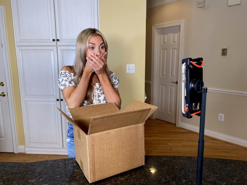 زنی با دست روی دهان مقابل جعبه باز و تلفن همراه ایستاده