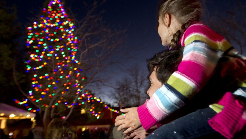 Five-year-old Darya Ilnytsky, from Poway, claps her hands just after the Christmas tree was lit as she sits on her dad's, Alex Ilnytsky, shoulders during the tree lighting ceremony at Pioneer Museum