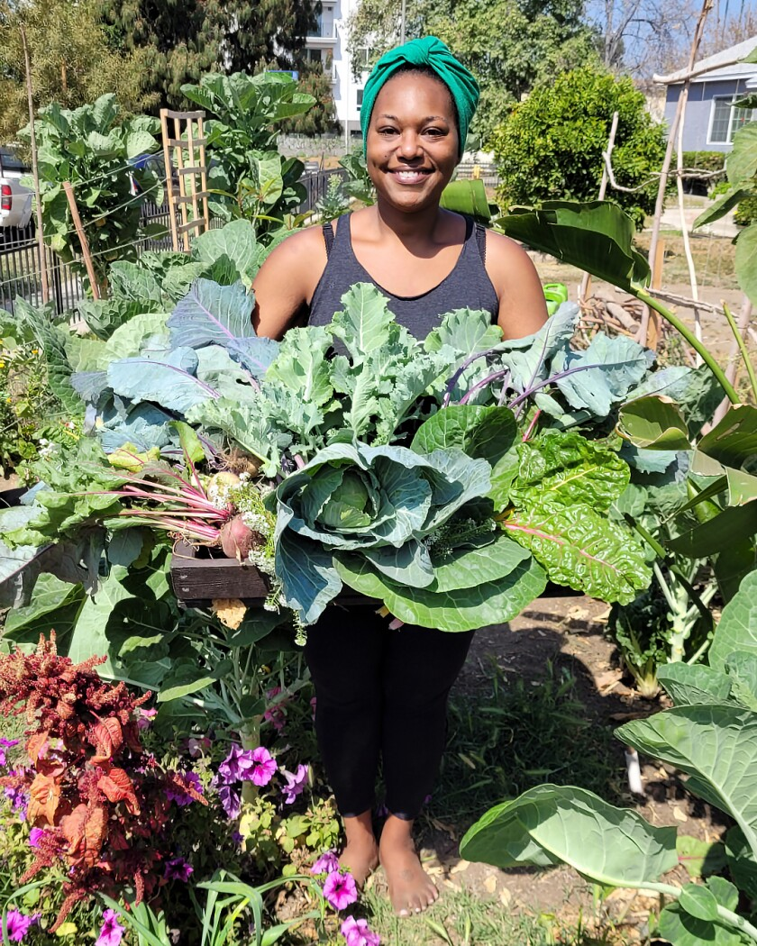 A woman in a garden holds a giant bunch of greens