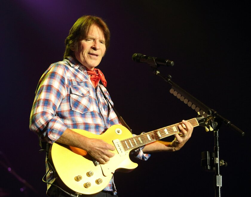 HOLD FOR STORY - FILE - In this July 18, 2014 file photo, singer-songwriter John Fogerty performs in concert at The Sands Event Center in Bethlehem, Pa. Fogerty is suing two of his former Creedence Clearwater Revival bandmates claiming they haven't paid him in years for performing the band's hits w