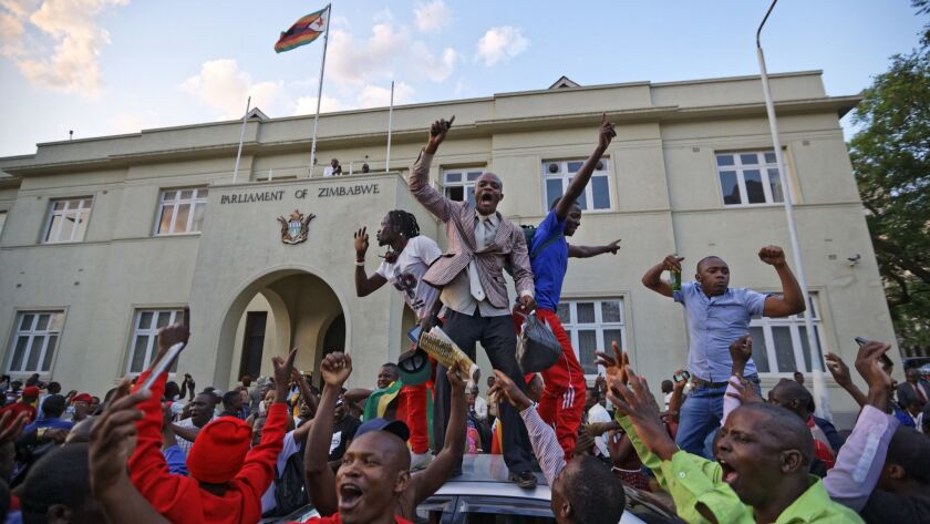 Zimbabweans celebrate outside the parliament building immediately after hearing the news that Presid