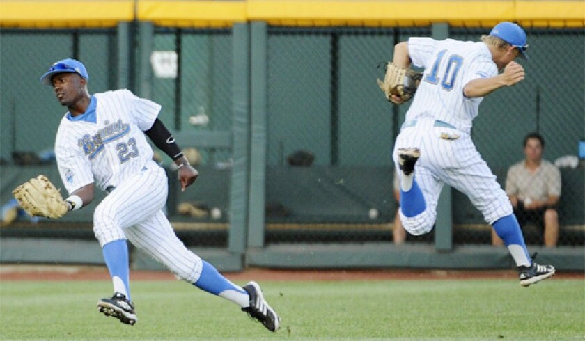 UCLA left fielder Brenton Allen, left, catches a fly ball as shortstop Pat Valaika runs in the opposite direction in the third inning of the Bruins' 4-1 victory over the Tarheels, punching their ticket for the College World Series championship round where they'll face Mississippi State.