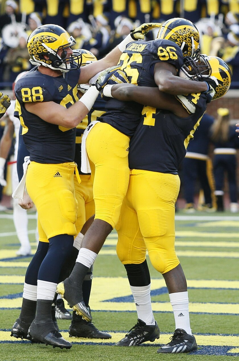 Michigan's Jehu Chesson (86) celebrates with A.J. Williams, right, and Jake Butt (88) after scoring a touchdown during the first half of an NCAA college football game against Rutgers, Saturday, Nov. 7, 2015, in Ann Arbor, Mich. (AP Photo/Duane Burleson)