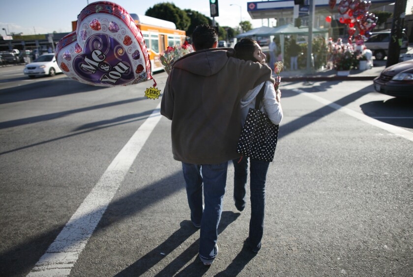 A couple cross 4th Street in Boyle Heights after purchasing balloons for Valentine's Day.