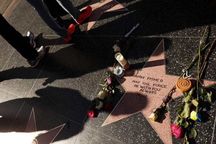 People observe a star that is dedicated to the memory of Star Wars actress Carrie Fisher on the Hollywood Walk of Fame.