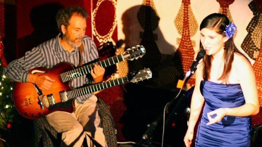 Guitarist Peter Sprague is shown performing with singer Nina Francis. Because of the wet weather, the 2019 edition of Sprague's free, 40-year-old annual Christmas Eve concert is being moved from its usual open-air location in Del Mar to an indoor venue in nearby Encinitas.