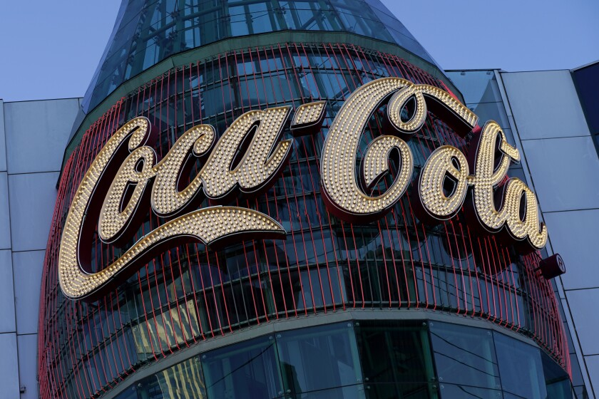In this Feb. 4, 2021, photo, a lighted sign adorns the Coca-Cola Store in Las Vegas. The resurgent coronavirus slowed Coca-Cola's recovery in the fourth quarter, and the company said the slump has continued into this year. (AP Photo/John Locher)