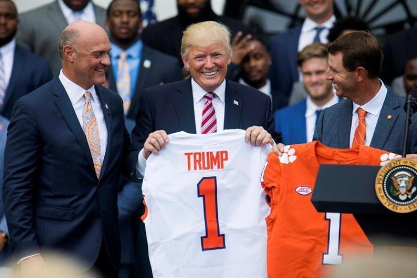 El presidente de EE.UU. Donald J. Trump (c), sostiene una camiseta de Clemson Tigers, junto al Director de la Universidad de Clemson, James Clements (i), y al entrenador de fútbol americano de Clemson, Dabo Swinney (d), durante el recibimiento de los Campeones Nacionales de Fútbol 2016, the Clemson Tigers, el lunes 12 de junio de 2017, en el patio sur de la Casa Blanca en Washington (EE.UU.). EFE/Archivo