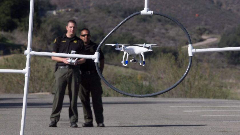 Sheriff's detectives David Chandroo, right, and Justin Crews, left, flew a drone through an obstacle course during training in Ramona in January.