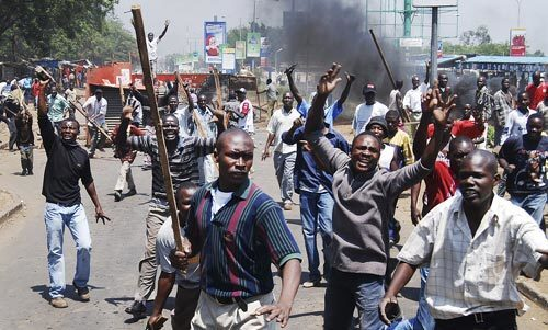 """Angry mobs clash with police in Kisumu and other Kenyan cities as news spread about the slaying of a second opposition lawmaker. The newly elected parliament member, David Kimutai Too, and a female companion were shot to death in a car in what police described as a """"crime of passion"""" arising from a love triangle."""