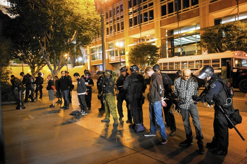 LAPD officers search protesters arrested in downtown Los Angeles on the third day of demonstrations over the failure to charge the Ferguson, Mo., police officer who shot Michael Brown to death.