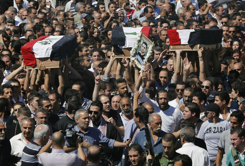 The coffins of three Syrian Christians killed last weekend in sectarian fighting in the ancient town of Maaloula are carried during a funeral march in Damascus on Tuesday. A UN Human Rights Council panel reported Wednesday that war crimes are on the rise among both Syrian government and rebel forces.