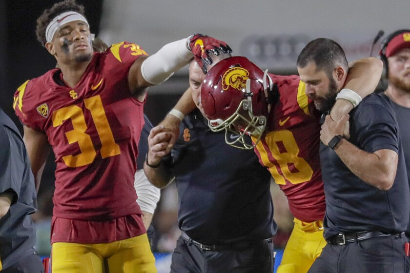 USC linebacker Hunter Echols reaches out to console quarterback JT Daniels as he is helped off the field late in the second quarter against Fresno State at the Coliseum.