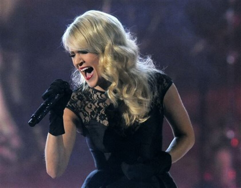 """FILE - This April 7, 2013 file photo shows Carrie Underwood performing at the 48th Annual Academy of Country Music Awards at the MGM Grand Garden Arena in Las Vegas. Underwood will take over the theme song for """"Sunday Night Football,"""" with NBC sticking to the formula of a female country music star for its intro. Underwood steps in for Faith Hill, who announced last month that she would not be back for a seventh season. Underwood will sing a new version of """"Waiting All Day for Sunday Night,"""" the"""