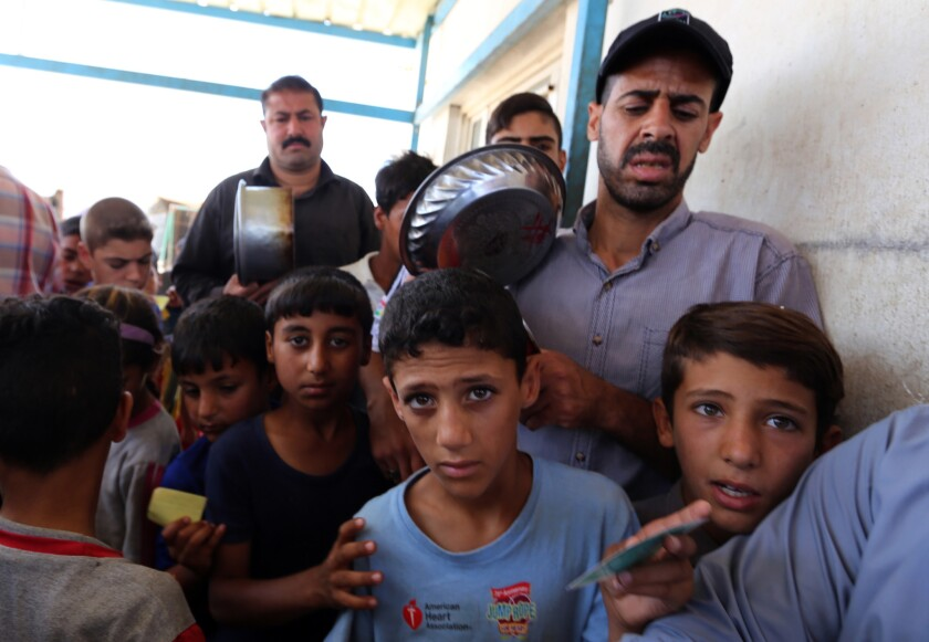 Displaced Iraqis who fled fighting between government forces and the Islamic State group in Anbar province line up to collect donated food at the Alexanzan camp in the Dora neighborhood on the southern outskirts of Baghdad on May 31, 2016.