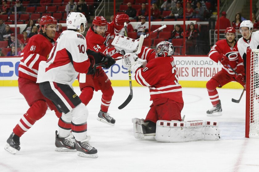 Carolina Hurricanes goaltender Cam Ward (30) and teammate Brett Pesce (54) make a save on a shot by Ottawa Senators' Shane Prince (10) as Hurricanes' Ron Hainsey, left, and Jay McClement, second from right, and Mark Stone, right, watch during the first period of an NHL hockey game in Raleigh, N.C.,