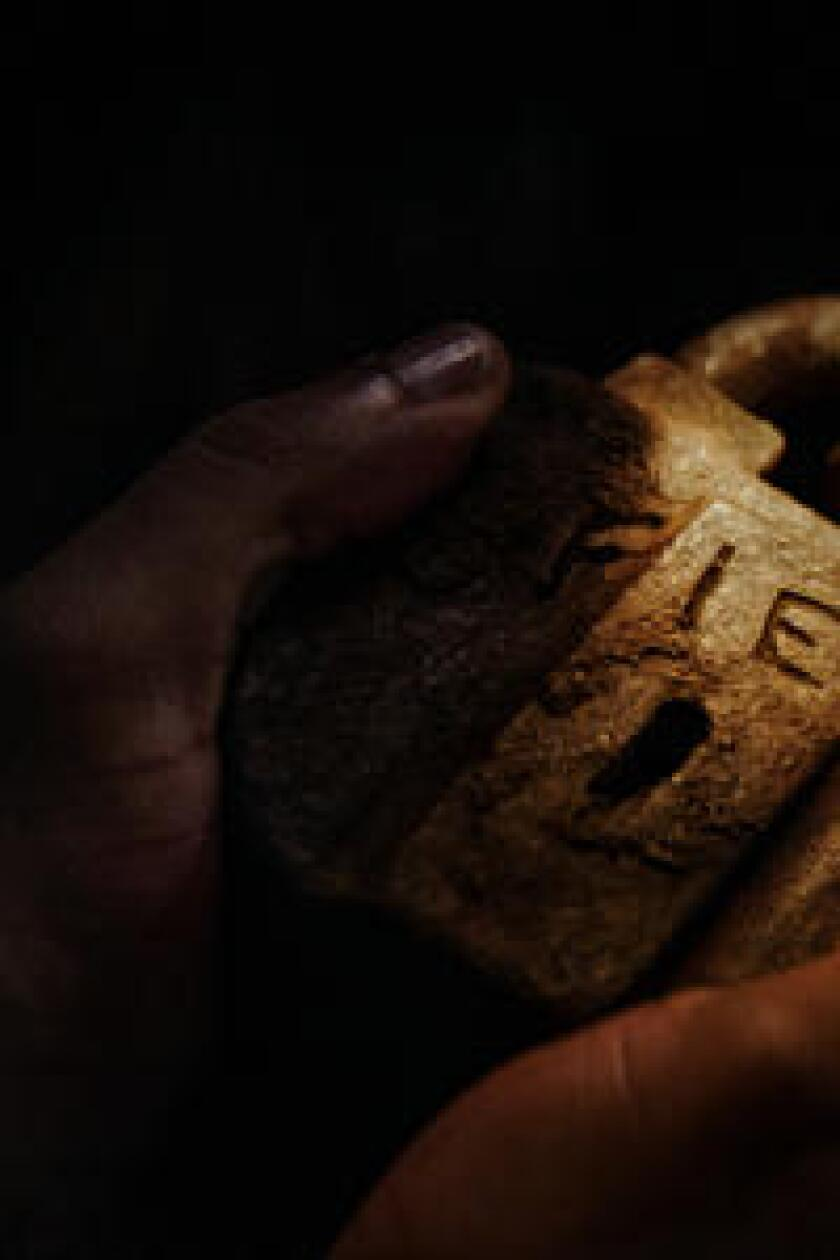 """A hand holds an object with the letters """"FIE"""" carved into it."""