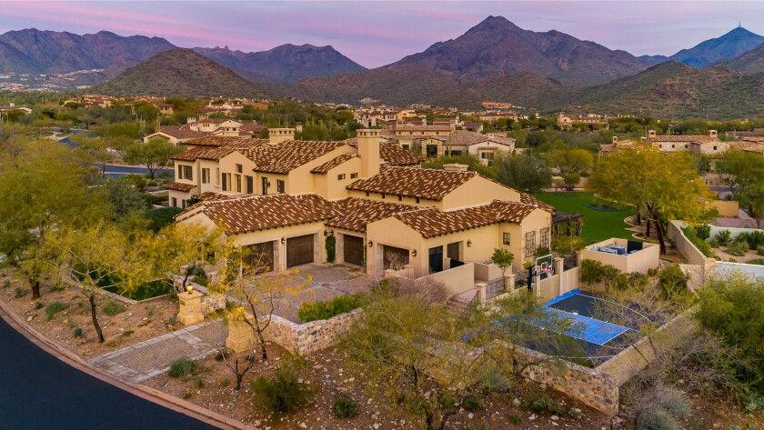 Bird's eye view of property with buildings surrounded by landscaping with hills and other homes in the background.