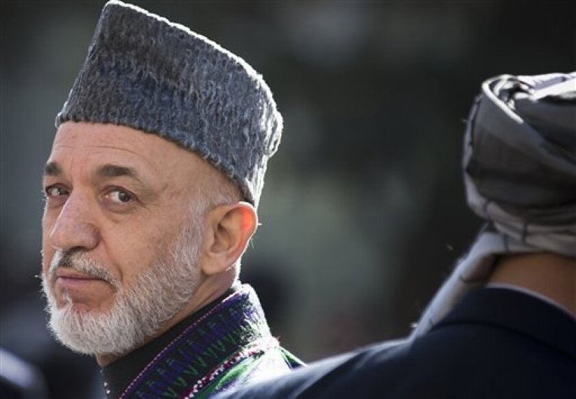 FILE- In this Friday, Oct 26, 2012 file photo, Afghan President Hamid Karzai turns around after reviewing the guard of honor during the first day of Eid Al Adha celebrations at the presidential palace in Kabul, Afghanistan. As the clock ticks toward 2014 and the final withdrawal of NATO and U.S. troops, peace talks with the Taliban are floundering even as the Taliban are showing some hopeful signs, attending international conferences and issuing a statement from their reclusive one-eyed leader with a surprise offer to share power in Afghanistan. (AP Photo/Anja Niedringhaus, File)