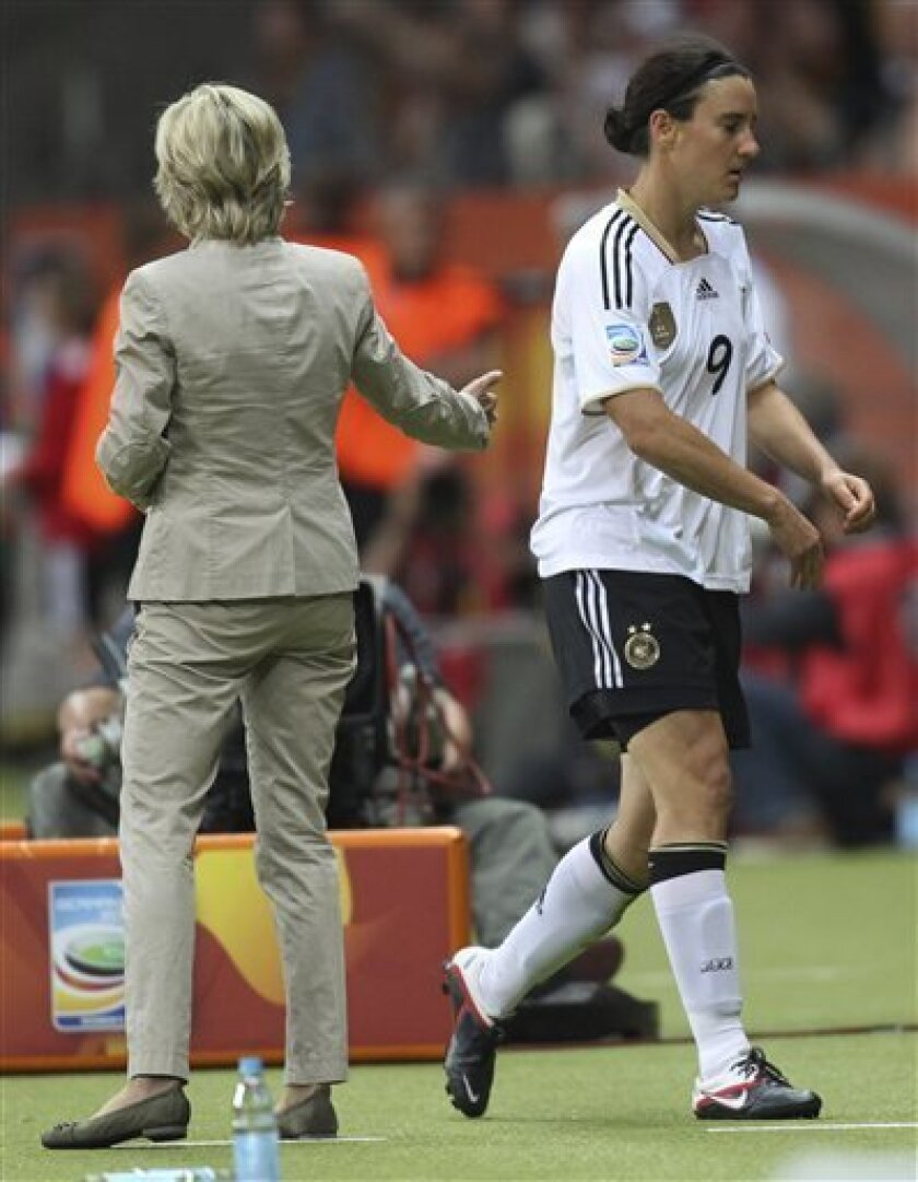 Germany's Birgit Prinz, right, leaves the field after being substituted as Germany team coach Silvia Neid looks on during the group A match between Germany and Nigeria at the Women's Soccer World Cup in Frankfurt, Germany, Thursday, June 30, 2011. (AP Photo/Michael Probst)