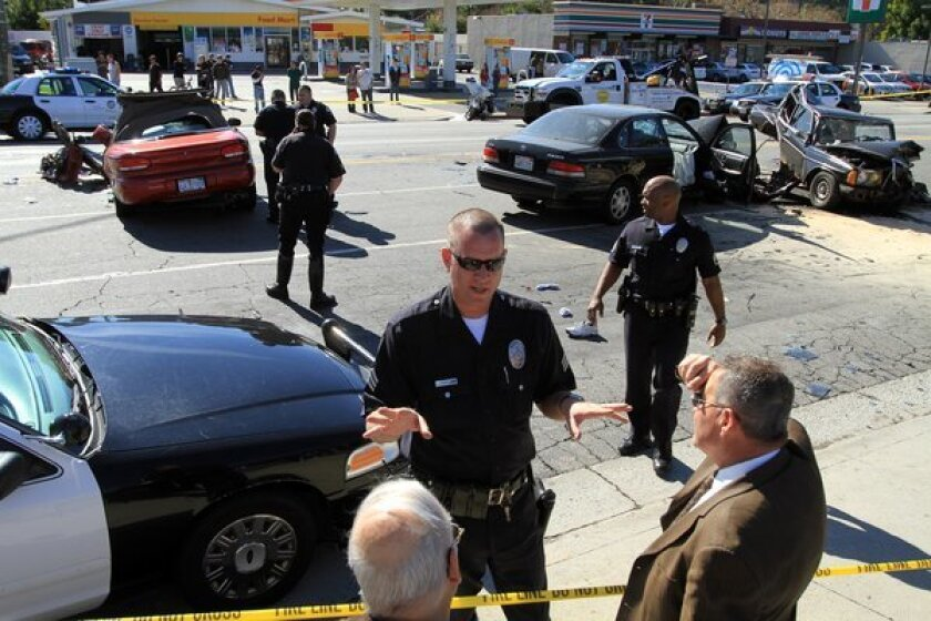 Police investigators work at the scene of a multi-vehicle hit-and-run accident involving four cars at De Soto Avenue and Ventura Boulevard in Los Angeles.