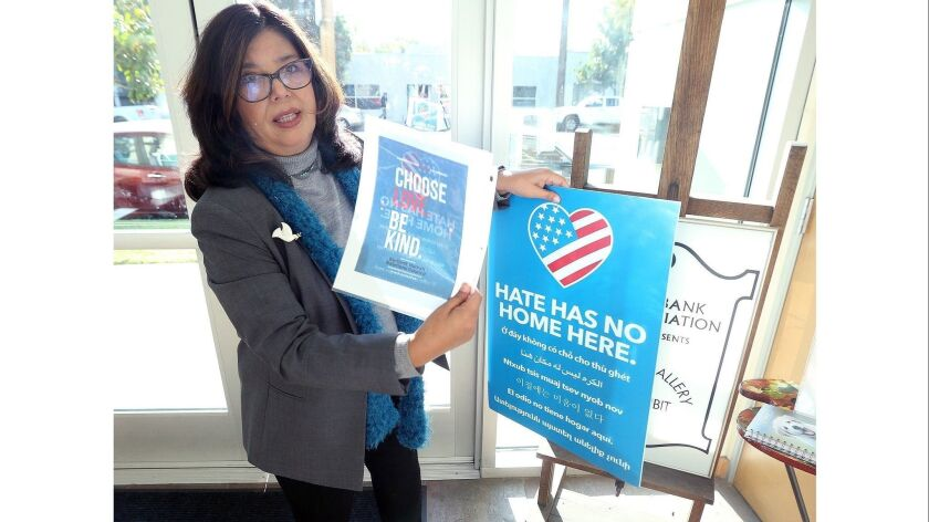 Marsha Ramos, of the Burbank Human Relations Council, holds a yard sign, and an image that will be o