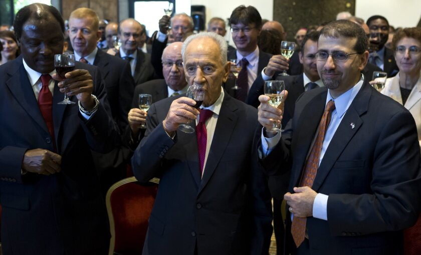 At approximately the same time that Israel was conducting a test of its missile-defense system, Israeli President Shimon Peres, center, was hosting foreign diplomats at his residence in Jerusalem, including U.S. Ambassador Dan Shapiro, right, and Cameroon Ambassador Henri Etoundi Essomba, to celebrate the pending Jewish new year, which begins Wednesday night.