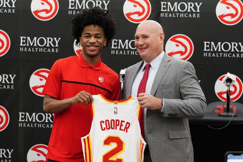Atlanta Hawks NBA basketball draft pick Sharife Cooper, left, and Hawks general manger Travis Schlenk poses for photos after a news conference Friday, July 30, 2021, in Atlanta. (AP Photo/John Bazemore)