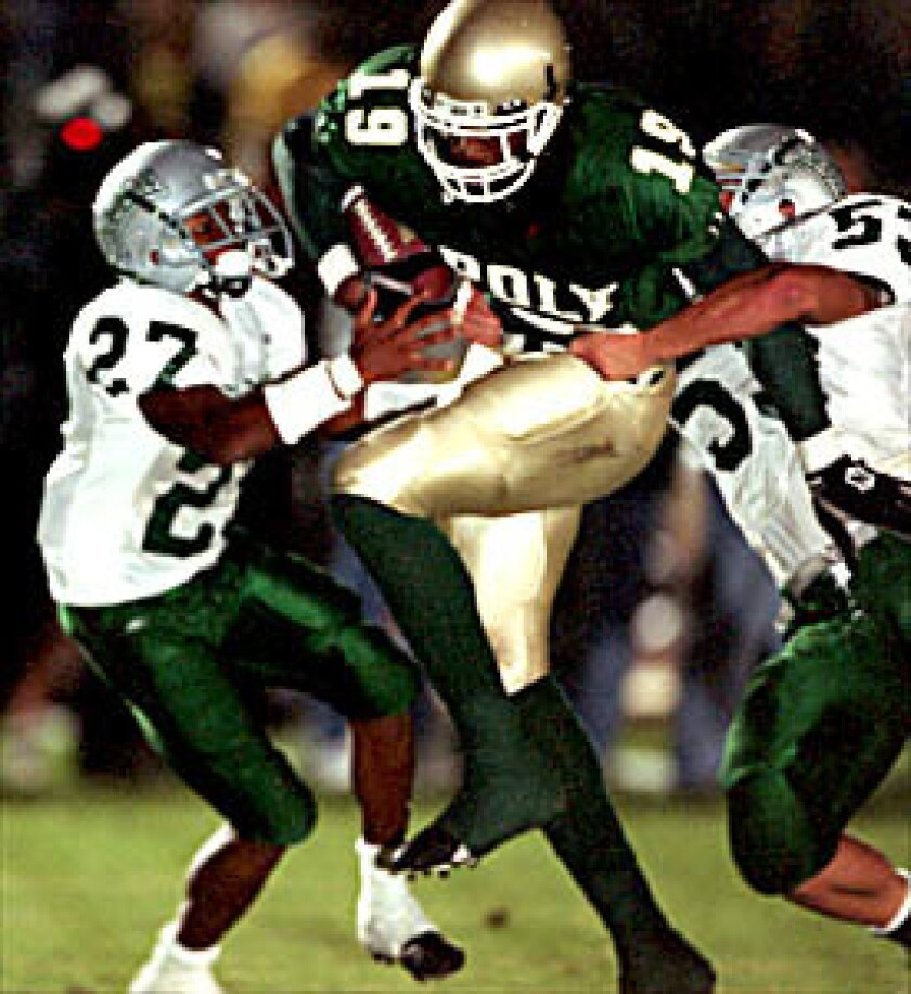 In 2001, Long Beach Poly's Marcedes Lewis tries to get by Concord De La Salle defenders Alijah Bradley (left) and Cole Smith.