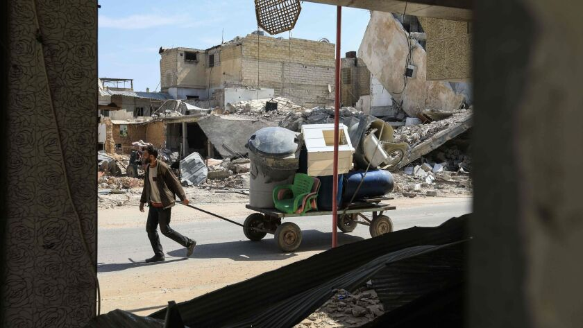 A Syrian man pulls a wagon filled with belongings as he flees his home in Douma.